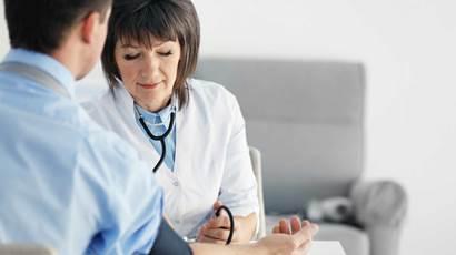 Female doctor measuring man blood pressure